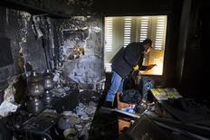 Funcionário conserta janela em sala danificada por um suposto incêndio criminoso na sede do time israelense Beitar Jerusalém, em Jerusalém. 08/02/2013 REUTERS/Ronen Zvulun