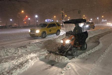A snow plow blows snow in New York , February 8, 2013. REUTERS/Keith Bedford