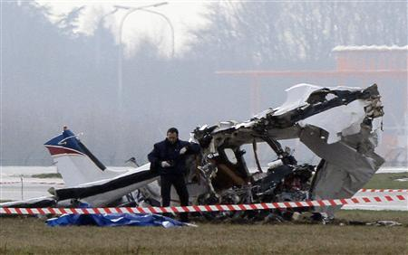 A police photographer inspects the scene of a tourist plane crash at Charleroi airport February 9, 2013. REUTERS/Sebastien Pirlet