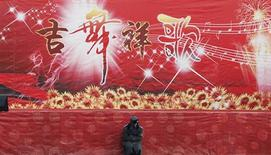A security guard sits in front of a stage during the temple fair in Ditan Park, also known as the Temple of Earth, in Beijing February 9, 2013. The Lunar New Year, or Spring Festival, begins on February 10 and marks the start of the Year of the Snake, according to the Chinese zodiac. REUTERS/Kim Kyung-Hoon