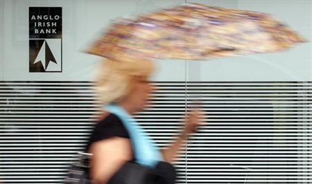 A woman is seen walking past a branch of the Anglo Irish Bank in Belfast in this September 28, 2010 file photograph. The European Central Bank moved towards agreeing a deal on February 7, 2013 to ease Ireland's debt burden after Dublin rushed through emergency legislation to liquidate the failed Anglo Irish Bank. REUTERS/Cathal McNaughton/Files (Northern Ireland - Tags: BUSINESS POLITICS)
