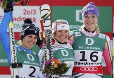 Second placed Nadia Fanchini of Italy (L), first placed Marion Rolland of France (C) and third placed Maria Hoefl-Riesch of Germany celebrate on the podium during the flower ceremony after the women's Downhill race at the World Alpine Skiing Championships in Schladming February 10, 2013. REUTERS/Leonhard Foeger