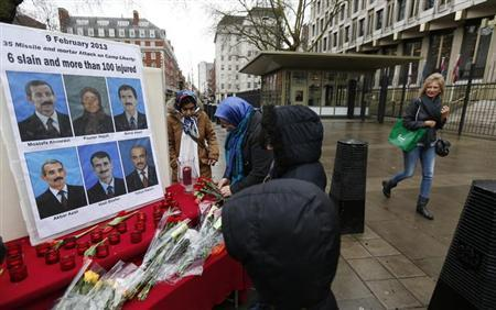 A pedestrian passes by a makeshift memorial erected by supporters of the People's Mojahedin Organization Of Iran (PMOI) during a demonstrattion outside the U.S. Embassy in London February 9, 2013. At least five people were killed and more than 25 wounded in a rocket attack on an Iranian dissident camp in Iraq's capital Baghdad early on Saturday, police sources said. REUTERS/Suzanne Plunkett (BRITAIN - Tags: CIVIL UNREST POLITICS)