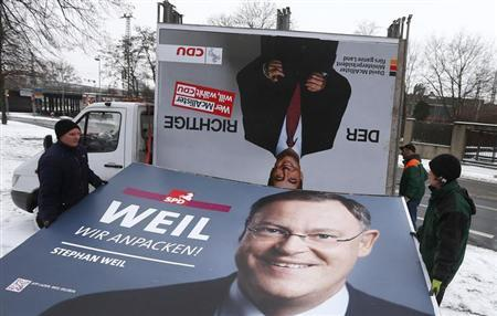 An election campaign placard of Christian Democratic Union (CDU) top candidate and outgoing state governor David McAllister is seen upside down on a truck as workers load the placard of Social Democratic Party (SPD) election winner Stephan Weil, the day after the state elections of Lower Saxony in Hanover January 21, 2013. REUTERS/ Kai Pfaffenbach (GERMANY - Tags: ELECTIONS POLITICS)