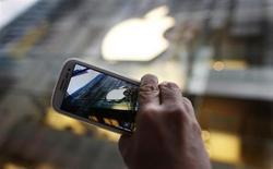 Un poderoso fabricante asiático, Samsung Electronics, emplea el sistema operativo Android de Google para crear teléfonos avanzados y tabletas con un gran parecido con el iPhone y el iPad. Samsung empieza a ganar cuota de mercado, dañando los márgenes de Apple y el valor de su acción y poniendo en peligro su reinado en el mundo de la electrónica de consumo. En la imagen de archivo, un transeúnte fotografía el logotipo de Apple en una tienda con su móvil Samsung en Sídney. REUTERS/Tim Wimborne