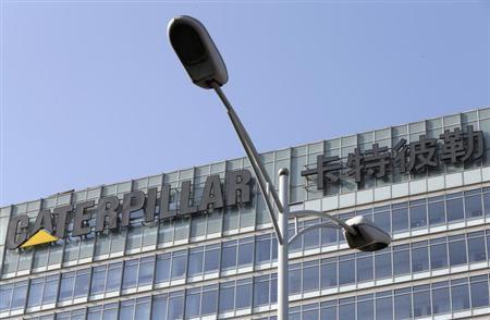The company logo is seen on top of a building, where Caterpillar (China) Investment Co., Ltd. is located, behind a street lamp, in Beijing, January 22, 2013. REUTERS/Jason Lee/Files