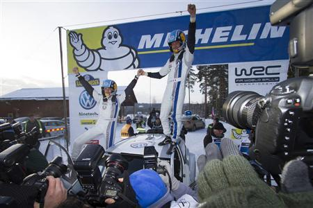 France's Sebastien Ogier (R) and his co-driver France's Julien Ingrassa celebrate as they stand on their VW Polo WRC after winning the Sweden Rally of the second round of the FIA World Rally Championship in Hagfors, in this February 10, 2013 picture taken by Scanpix. REUTERS/Micke Fransson/Scanpix Sweden