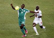 Contrôle du Nigérian Sunday Mba sous le regard de Djakaridja Koné (à droite) du Burkina Faso, à Johannesburg. Le Nigeria a remporté dimanche la Coupe d'Afrique des nations (Can) pour la troisième fois de son histoire en battant en finale le Burkina Faso grâce à un but de Sunday Mba en première période (1-0). /Photo prise le 10 février 2013/REUTERS/Siphiwe Sibeko