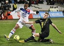Le Lyonnais Alexandre Lacazette (à gauche) en duel avec le Lillois Lucas Digne, au stade Gerland. Pour le deuxième week-end de suite, les deux Olympiques de Ligue 1 ont réalisé chacun une contre-performance dimanche, une défaite à domicile contre Lille pour Lyon (3-1) et un match nul à Evian pour Marseille (1-1). /Photo prise le 10 février 2013/REUTERS/Robert Pratta