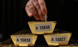 Сотрудник Бундесбанка проверяет слитки золота на пресс-конференции во Франкфурте-на-Майне 16 января 2013 года. Цены на золото стоят на месте, а платина и палладий близки к максимумам 17 месяцев. REUTERS/Lisi Niesner