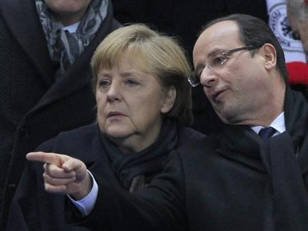 France's President Francois Hollande (R) and German Chancellor Angela Merkel speak as they attend an international friendly soccer match between France and Germany at the Stade de France stadium in Saint-Denis, near Paris, February 6, 2013. REUTERS/Gonzalo Fuentes