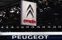 Peugeot and Citroen logos are seen over the French carmakers' showcases on media day at the Paris Mondial de l'Automobile, September 28, 2012. REUTERS/Christian Hartmann