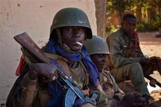 Tropas malienses registraban casa por casa en Gao el lunes en busca de insurgentes islamistas, cuyo ataque durante el fin de semana en la localidad norteña mostró el riesgo de que las tropas francesas se vean inmersas en una compleja guerra de guerrillas. En la imagen, un soldado maliense sostiene en la boca un cigarrillo sin encender durante tiroteos con insurgentes islamistas en la ciudad de Gao, en Mali, el 10 de febrero de 2013. REUTERS/François Rihouay
