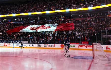 Toronto Maple Leafs goalie James Reimer stands while the Canadian national anthem is played as fans hold a giant Canadian flag before his team plays the Philadelphia Flyers in their NHL hockey game in Toronto, February 11, 2013. REUTERS/Mark Blinch
