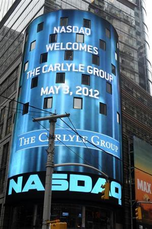 Passersby walk in front of video monitors announcing the Carlyle Group's listing on the NASDAQ market site in New York's Times Square after the opening bell for trading, May 3, 2012. REUTERS/Keith Bedford (UNITED STATES - Tags: BUSINESS)