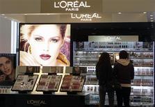 Посетители парфюмерного магазина в Риге стоят у секции L'Oreal 13 апреля 2012 года. Крупнейший в мире производитель косметики L'Oreal потратит около 500 миллионов евро на выкуп акций после публикации данных об ускорении квартальных сравнимых продаж. REUTERS/Ints Kalnins