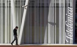 España ha registrado en 2012 la mayor caída del mercado móvil en su historia al darse de baja unos 2,75 millones de líneas móviles y datacards, de acuerdo con los datos publicados el martes por el regulador, la Comisión del mercado de las Telecomunicaciones. En la imagen, de 30 de enero, un hombre habla por teléfono cerca del edificio de Telefónica en Barcelona. REUTERS/Albert Gea