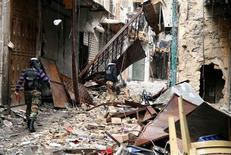Combatientes opositores sirios capturaron un aeropuerto militar cercano a la ciudad de Alepo el martes, en otro revés para las fuerzas del presidente Bashar el Asad, que han sufrido cada vez más ataques en todo el país. En la imagen, miembros del Ejército Libre Sirio caminan por escombros y edificios dañados cerca de la mezquita de Ymayad en Alepo, el 11 de febrero de 2013. REUTERS/Aref Heretani