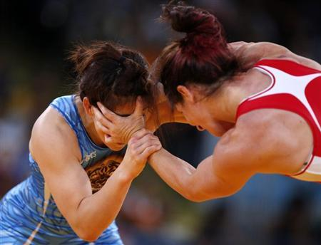 Japan's Saori Yoshida (in blue) fights with Canada's Tonya Lynn Verbeek on the final of the Women's 55Kg Freestyle wrestling at the ExCel venue during the London 2012 Olympic Games August 9, 2012. REUTERS/Damir Sagolj/Files