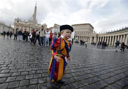 A child dressed as a Swiss Guard stands in St Peter's Square at the Vatican February 12, 2013. REUTERS/Max Rossi
