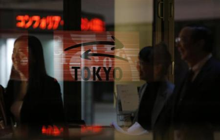 Visitors walk past a logo at the Tokyo Stock Exchange in Tokyo February 6, 2013. REUTERS/Toru Hanai/Files