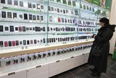 Женщина изучает витрину с мобильными телефонами в магазине Мегафона в Санкт-Петербурге 15 ноября 2012 года. Продажи мобильных телефонов по всему миру упали в 2012 году впервые с 2009 года, поскольку потребители избегали покупки более дешевой продукции, сообщила исследовательская компания Gartner. REUTERS/Alexander Demianchuk