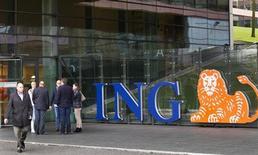 El banco y grupo de seguros holandés ING anunció otros 2.400 recortes de empleos en Holanda y Bélgica, mientras se prepara para separar sus operaciones bancarias y de seguros en un contexto de mercados financieros difíciles. En la imagen de archivo, empleados del grupo ING frente a su oficina en Amsterdam, el 7 de noviembre de 2012. REUTERS/Michael Kooren