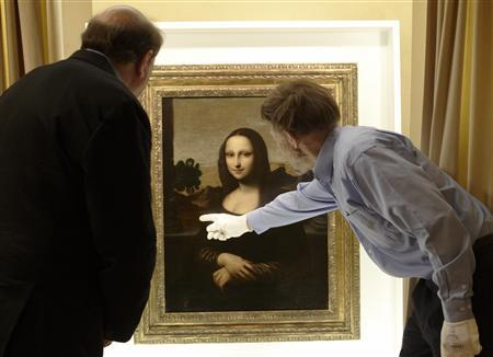 David Feldman (R) , vice president of the Mona Lisa Foundation, shows similarities on a painting attributed to Leonardo da Vinci and depicting Mona Lisa to his brother Stanley, an art historian, during a preview presentation in a vault in Geneva in this September 26, 2012 file photo. REUTERS/Denis Balibouse/Files