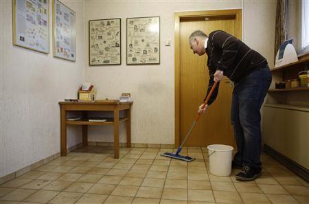 Peter Breiter, CEO of Raiffeisen Gammesfeld eG bank, washes the floor in the waiting room of the bank in Gammesfeld, Baden-Wuerttemberg January 29, 2013. REUTERS/Lisi Niesner