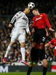 El delantero del Real Madrid Cristiano Ronaldo logró el miércoles un empate 1-1 en su partido contra el Manchester United, un encuentro de ida de octavos de final de la Liga de Campeones. En la imagen, el jugador del Real Madrid Cristiano Ronaldo (a la izquierda) y el del Manchester United Robin van Persie se disputan el balón durante su partido de ida de octavos de final de la Liga de Campeones, en Madrid, el 13 de febrero de 2013. REUTERS/Juan Medina