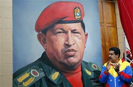 Venezuelan Vice President Nicolas Maduro claps his hands next to a painting of President Hugo Chavez during the commemoration of the 21st anniversary of Chavez's attempted coup d'etat in Caracas February 4, 2013. REUTERS/Jorge Silva