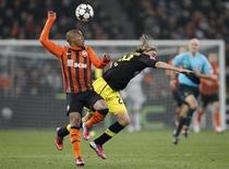 O brasileiro do Shakhtar Donetsk Douglas Costa disputa bola com o jogador do Borussia Dortmund Marcel Schmelzer durante empate dos times pela Liga dos Campeões. REUTERS/Gleb Garanich