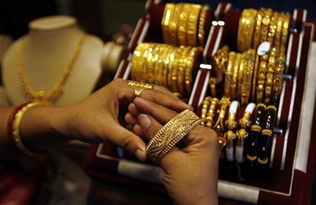 A woman wears a gold bangle at a jewellery shop in Siliguri October 1, 2008. REUTERS/Rupak De Chowdhuri/Files
