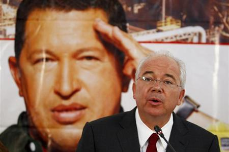 Venezuela's Energy Minister Rafael Ramirez talks to the media in front of a giant picture of Venezuela's President Hugo Chavez during a news conference at the headquarters of the state-run oil company PDVSA in Caracas February 13, 2013. REUTERS/Carlos Garcia Rawlins (VENEZUELA - Tags: POLITICS ENERGY)