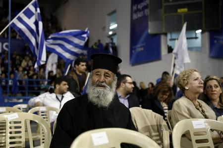 An Orthodox priest attends a pre-election rally by Cyprus presidential candidate Nicos Anastasiades in Nicosia February 13, 2013. REUTERS/Yorgos Karahalis