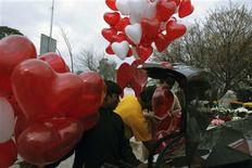 Men try to fit heart-shaped balloons in the trunk of a car on Valentine's Day in Islamabad February 14, 2013. REUTERS/Zohra Bensemra