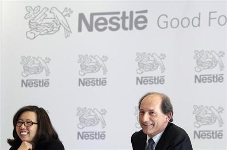 Nestle Chief Executive Officer Paul Bulcke (R) smiles next to CFO Wan Ling Martello during the annual results news conference at the company headquarters in Vevey February 14, 2013. REUTERS/Denis Balibouse