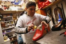 Shoemaker Antonio Arellano works on a red shoe he made for Pope Benedict XVI in his shop in downtown Rome February 14, 2013. Far from the designer stores on the other side of the Tiber, Arellano's shop, with its smell of glue and racks of shoe polish, is unremarkable, except for the fact that, due to its location, he counts Benedict as a loyal customer. With Benedict set to retire to an apartment inside the Vatican City, Arellano hopes he will remain his customer, even if the pope no longer visits in person. REUTERS/Tony Gentile