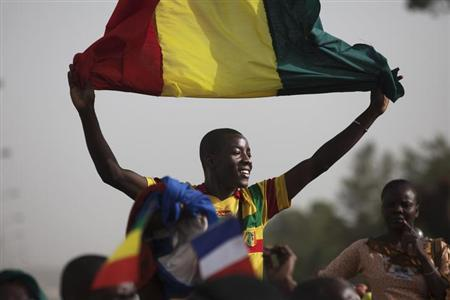 A Malian man waves a Mali flag as France's President Francois Hollande (not pictured) speaks at Independence Plaza in Bamako, Mali February 2, 2013. REUTERS/Joe Penney (MALI - Tags: POLITICS CONFLICT)