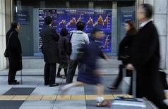 El Índice Nikkei cayó el viernes por una reducción de la exposición a los exportadores y los bancos, mientras que los inversores esperaban la reunión del G20 del fin de semana. En la imagen, varias personas pasan junto a un panel que muestra un índie bursátil en Tokio, el 30 de enero de 2013. REUTERS/Toru Hanai