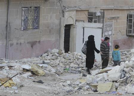 A family walk through rubble in the Al-Massir area in Aleppo February 13, 2013. REUTERS/Muzaffar Salman