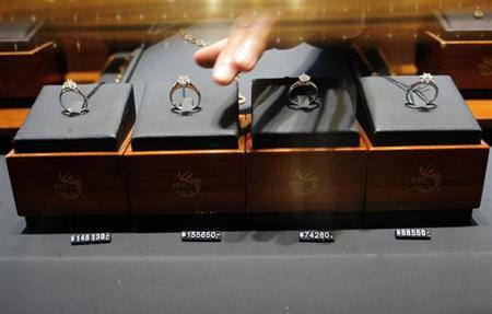 A shop assistant takes a diamond ring at a jewellery store in Hefei, Anhui province January 24, 2010. REUTERS/Stringer/Files