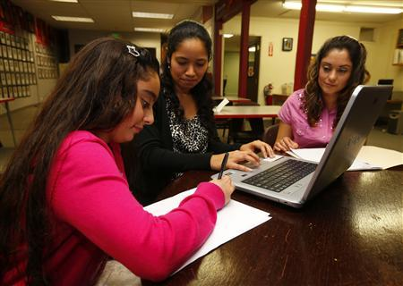 Teresa Villanueva (R) and her 11-year-old daughter Laritza receive help on their charter school application from Barrio Logan College Institute counselor Jennifer Pena (L) in San Diego, California, February 7, 2013. REUTERS/Mike Blake