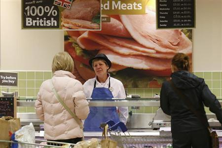 A worker serves customers in the meat department at a Tesco store in Bishop's Stortford, southern England November 26, 2012. REUTERS/Suzanne Plunkett