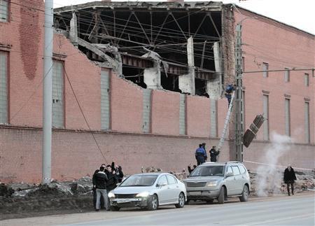 Workers repair damage caused after a meteorite passed above the Urals city of Chelyabinsk February 15, 2013. REUTERS/Yevgeni Yemeldinov