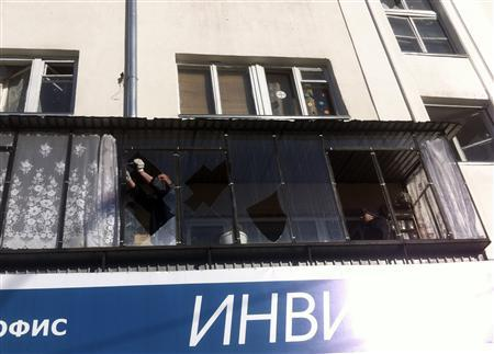 A man removes shards of glass from the frame of a broken window following sightings of a falling object in the sky in the Urals city of Chelyabinsk February 15, 2013. REUTERS/Andrei Kuzmin