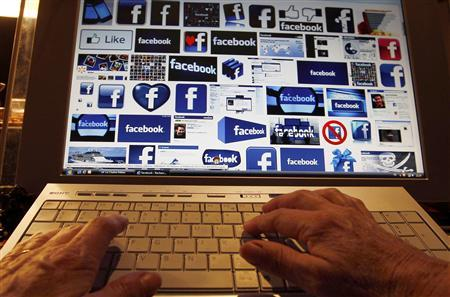 A women works with her computer which displays Facebook logos on the screen in Bordeaux, Southwestern France, January 30, 2013. REUTERS/Regis Duvignau
