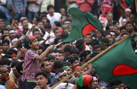 A boy waves a Bangladesh national flag as he chants a slogan before a mass funeral as the body of Rajib Haider, an architect and blogger who was a key figure in organising demonstrations, arrives at Shahbagh intersection in Dhaka February 16, 2013. REUTERS/Andrew Biraj