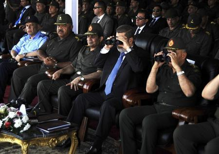 Egypt's President Mohamed Mursi (2nd R) uses a pair of binoculars as he sits next to Defence Minister Abdel Fattah al-Sisi (3rd L) and General Sedky Sobhi (R), chief of staff to Egypt's Supreme Council of the Armed Forces (SCAF), during his visit to the 6th armoured division of the second army, near Ismailia, some 75 miles (121 km) north of Cairo October 10, 2012. REUTERS/Egyptian Presidency/Handout