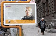 A woman walks by an election poster of the presidential candidate Raffi Hovannisin in Yerevan, February 17, 2013. REUTERS/David Mdzinarishvili